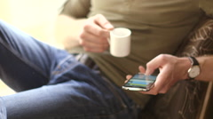 Young man texting on a smatphone in cafe drinking coffee Stock Footage