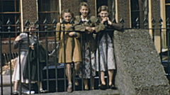 England 1955: little girls watching a football game from outside the ground Stock Footage