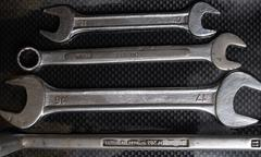 Nut wrenches on a reflective carbon fiber surface - stock photo