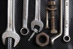 Nut wrenches on carbon fiber with nuts and bolts - stock photo