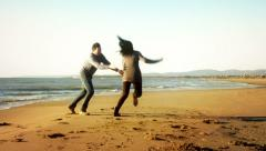 Man trying to catch girlfriend on beach slow motion at sunset Stock Footage