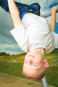 Child in playground kid in action boy play on leisure equipment Stock Photos
