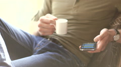 Young man texting on a smatphone in cafe drinking coffee - stock footage