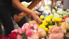 Brazilian mother and daughter look at flowers at a market - stock footage