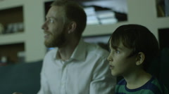 Father plays a video game with son after a long day at work - stock footage