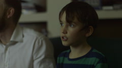 Father plays a video game with son after a long day at work Stock Footage