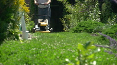 Man mowing lawn, that classic summer sound of a 2-stroke gas mower Stock Footage