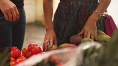 Mother and daughter pick fresh produce at a street market Stock Footage