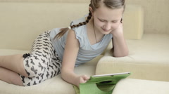 Innocent blonde ponytail white skin girl playing using tablet lie on cream sofa - stock footage