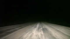 Car driving through the night on winter road. Visibility limited by headlight - stock footage