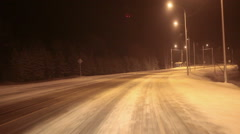 Car driving at night through the illuminated part of snowy freeway Stock Footage