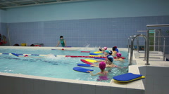 Kids are on swimming exercises in pool. Preschool children swimming training Stock Footage