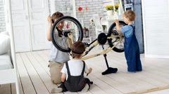 Stock Video Footage of 3 Children repairing a bicycle in a village house