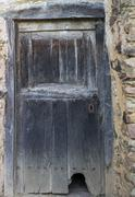 Entire old wooden door with cathole (cat flap) - stock photo