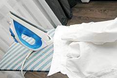 White collar shirt and iron on ironing board Stock Photos