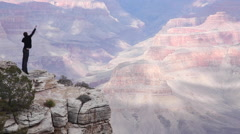 Man fist pumps at edge of Grand Canyon - motivational! - stock footage