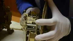 Watchmaker with white gloves overhauls mechanical system of antique pendulum Stock Footage