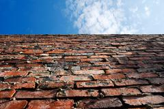 old brick wall and blue sky - stock photo