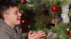 Pap throws up baby near Christmas tree Stock Footage