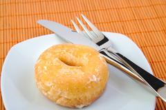 Glazed donut with fork and knife. Doughnut. Stock Photos