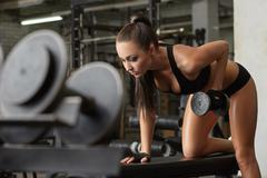 Exciting brunette exercising with dumbbells in gym - stock photo