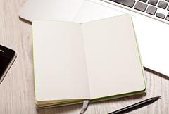 open notepad with blank pages on table with laptop - stock photo