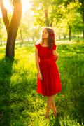 Pretty young women in red dress backlit by sunset in front of green trees. Stock Photos