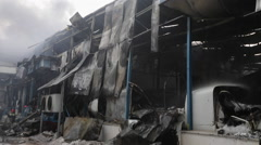 A burned out building smolders after a fire. Stock Footage
