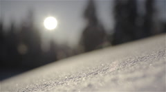 Snow crystals sparkling in the foreground as camera slowly pans Stock Footage