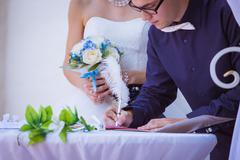Groom signing wedding certificate in park Stock Photos