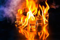 Glasses with burning alcohol on black background Stock Photos