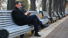 A man in a black coat with a tablet walk in the autumn park Stock Footage