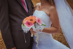 Wedding couple hugging, the bride holding a bouquet of flowers in her hand, t Stock Photos