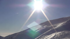 Sun shining over a mountain slope with deep snow . Winter holiday season. - stock footage