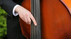 Man Strumming Double Bass Outside Stock Footage