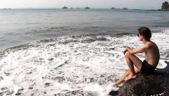 Man Sitting on the Rock at the Beach 2 Stock Footage