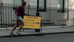 Woman runs past Olympic 2012 sign. Stock Footage