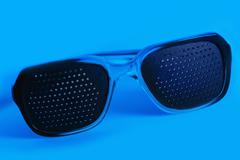 medical spectacles with hole in blue backgrounds - stock photo