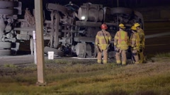 Semi on its side after a crash. Fire personnel on scene - stock footage