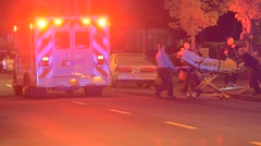 Patient being loaded into the back of an ambulance - stock footage