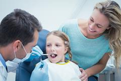 Dentist examining girls teeth with assistant Stock Photos