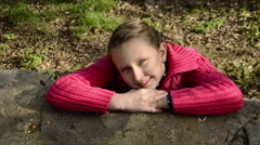 Beautiful blue eye ponytails blonde small smiling teen girl lean on rock at park Stock Footage