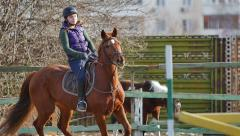 Professional female jockey rides on horseback Stock Footage