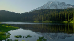 Mount Rainier reflecting in lake at sunrise Stock Footage