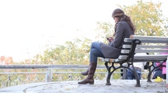 Girl sitting on the bench and writes sms Stock Footage