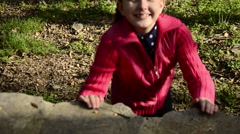 Beautiful blue eye ponytails blonde small smiling girl lean on rock at park Stock Footage
