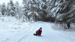 Tired caucasian little boy climbs on a snowy mountain on all fours Stock Footage