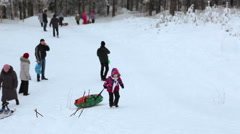 Caucasian small girl pulls the tubing for the rope on a snowy mountain Stock Footage