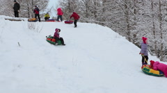 Caucasian girl rolling on the tubing from the mountain to the mother Stock Footage