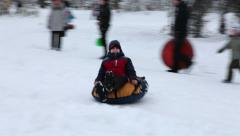 Russian kids on a winter walk roll down the hill in the snow on the tubing Stock Footage